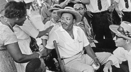Surrounded by press and supporters during a break in the Meredith March Against Fear, Martin Luther King Jr. shakes hands with civil rights activist and Mississippi leader Annie Devine. Canton, Mississippi, 1966 (detail). Photograph by Bob Fitch; copyright Stanford University Libraries.
