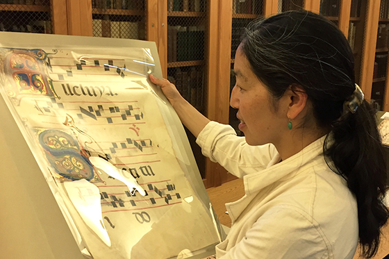 "Instructor Heidi Lee examines an antiphonary leaf during the ""Why Music Matters"" course. Image courtesy of Ray Heigemeir/Stanford Libraries."