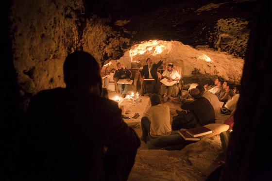 Kabbalist Rabi Uri Revach, second left, sits in front of his students during overnight Kabbalah studies inside a Jerusalem mountain cave near the village of Beit Meir on May 7, 2010. About a dozen of Orthodox Jewish men gather once a week in the cave near the holy city to study all night long the ancient Jewish mystical rite of Kabbalah, reading texts from Jewish holy books, including the Zohar texts. MENAHEM KAHANA/AFP/GETTY.